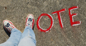 """VOTE"" with a person's feet making the letter V"